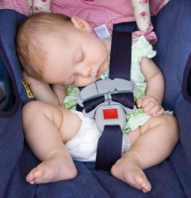 Newborn baby girl slouched over and sound asleep in her car seat.